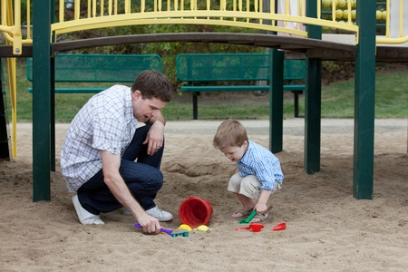 Happy Father And Son Playing At Playground In Sand With Toys. photo