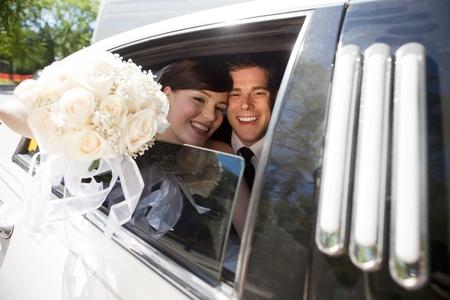протяжение: Портрет молодоженов улыбается, сидя в лимузине Букет держит в руке.