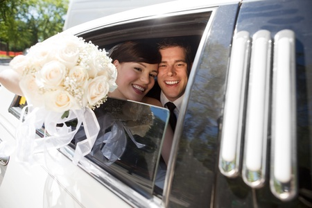 stretches: Portrait Of Newlywed Couple Smiling Sitting In Limousine Holding Bouquet In Hand. Stock Photo