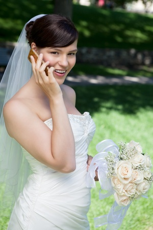 Happy bride talking on cell phone in wedding dress photo