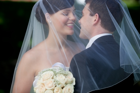 Bride And Groom Kissing Under Veil Holding Flower Bouquet In Hand. photo
