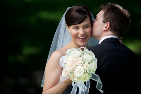 wedding portrait: Newlywed Couple Kissing Each Other Holding Flower Bouquet In Hand.