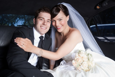 Portrait Of Newlywed Couple Smiling Sitting In Limousine. photo
