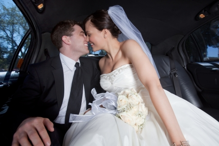 Newlywed couple kissing inside a luxurious limousine photo