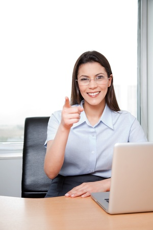 Portrait Of A Young Businesswoman Pointing At The Viewer In Her Office. photo