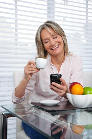 mid morning: Smiling mature woman using cell phone while having tea Stock Photo