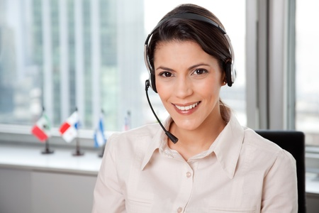 sales call: Young Business Woman With Headset In Office.