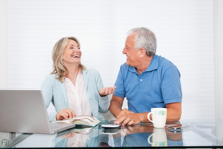 Happy couple at dining table working on laptop on house finance photo