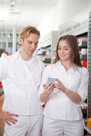 Two Pharmacists With Pharmaceuticals In Hand Consulting Each Other In A Pharmacy. photo