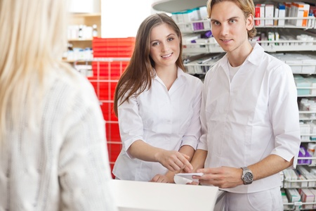 Portrait of two pharmacists at counter with customer photo