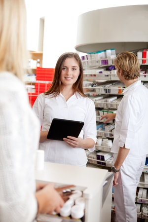 Portrait Of Female Pharmacist Holding Tablet Pc While Attending Customer. photo