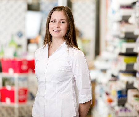 Portrait of a young attractive pharmacist standing in a pharmacy interior looking at the camera photo