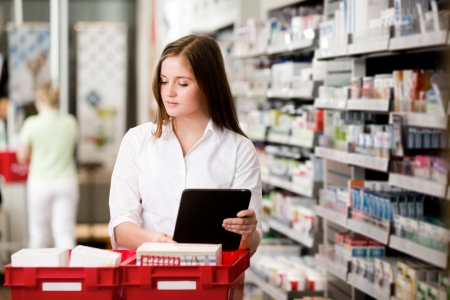 Female pharmacist working in pharmacy with digital tablet and medicine photo