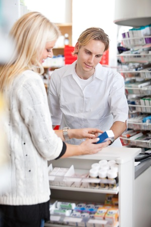 Male pharmacist helping female customer for medicine photo