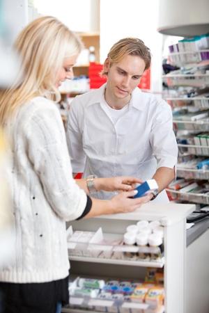 Male pharmacist helping female customer for medicine Stock Photo - 12382201