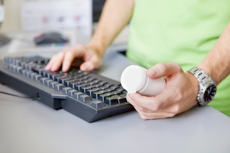Cropped image of male hand holding medicine container while typing on keyboard photo