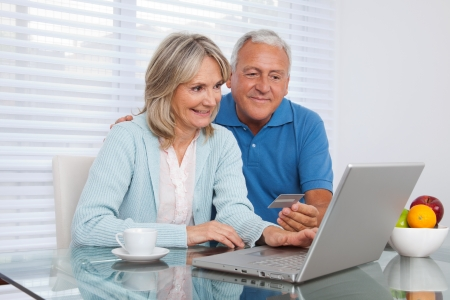 pensions: Senior couple shopping online using laptop with credit card