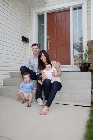 welcome home: Portrait Of Sweet Family Sitting In Front Of Their House