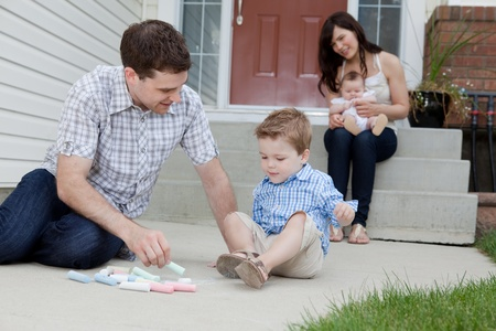 Young Father And Son Drawing With Chalk And Mother Sitting With Baby At Background In Front Of Their House  photo
