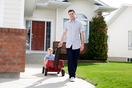 Father pulling son in a wagon in front of house on sidewalk photo