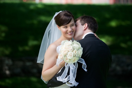 Newlywed Couple Kissing Each Other Holding Flower Bouquet In Hand  photo