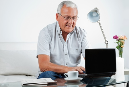 using a laptop: Senior man working on laptop at home