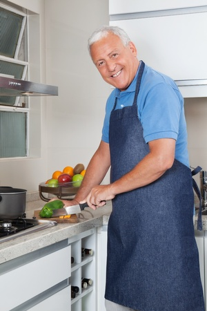 aprons: Portrait of smiling senior man cutting vegetables at kitchen counter