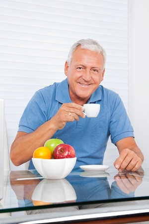 Portrait of smiling senior man having cup of tea photo