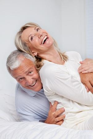 ベッドに一緒に笑っている年配のカップルの励起