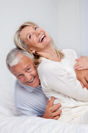 senior home: Excited senior couple laughing together on bed