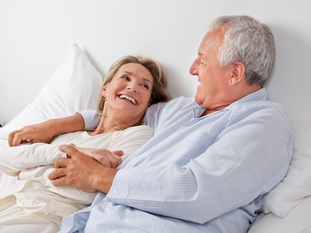 Cheerful couple relaxing on bed at home photo