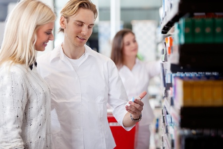 Pharmacist And Customers At Pharmacy In Front Of Shelves With Pharmaceuticals  photo