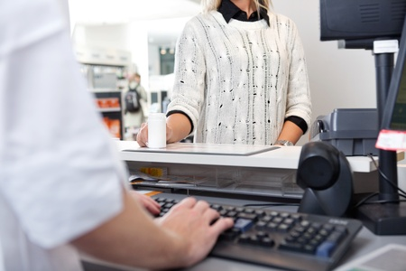 cashier: Mid-section of customer standing at checkout counter in drugstore