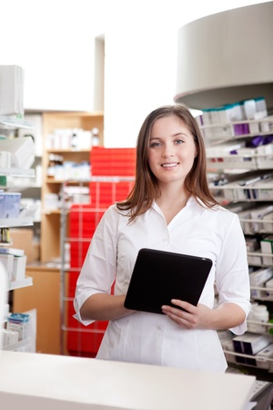 Portrait Of Smiling Female Pharmacist Holding Tablet Pc In Drugstore  photo