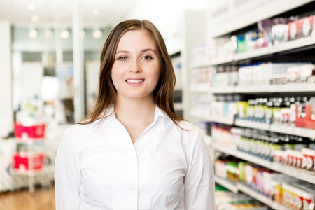 Portrait of a young attractive pharmacist looking at the camera in a pharmacy photo