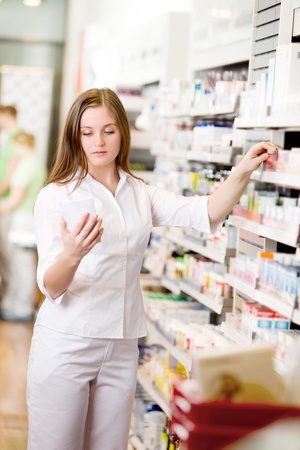 Attractive young pharmacist in pharmacy looking at prescription photo
