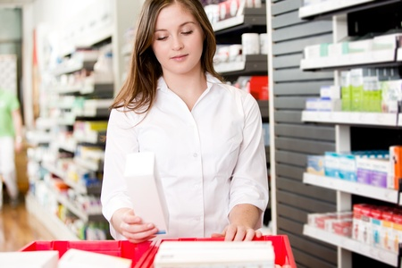 Pharmacist stocking shelves in pharmacy with box of medicine photo