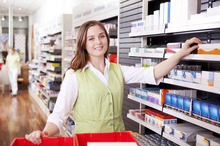 Young femail pharmacist looking for medicine in drugstore Stock Photo - 12382430
