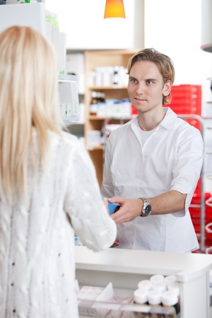 prescribe: Male Pharmacist With A Female Customer In Pharmacy Drugstore  Stock Photo