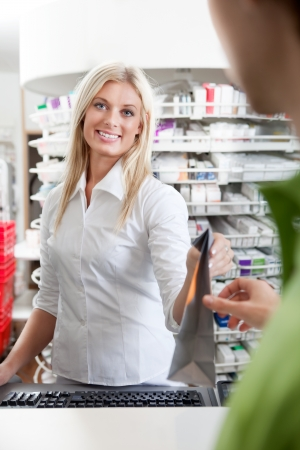 Female Pharmacist With Male Customer In Pharmacy Drugstore  photo