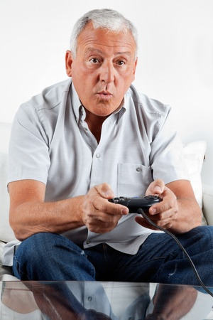Elderly man playing video game at home photo