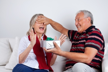 Senior man covering his wife s eyes to surprise her with a gift photo