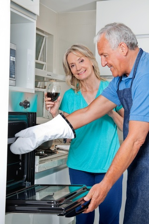 Senior couple in kitchen preparing meal together photo