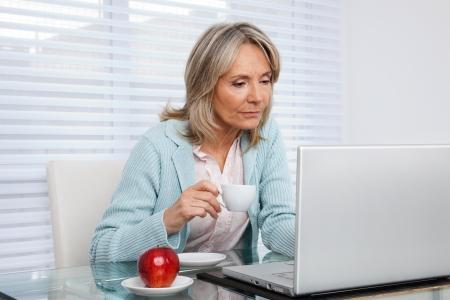 senior ordinateur: Femme d'�ge m�r travaillant sur ordinateur portable tout en tenant une tasse de th�