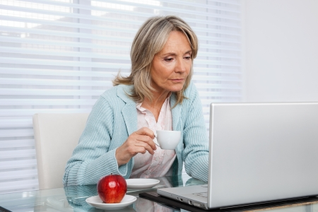 mid morning: Mature woman working on laptop while holding cup of tea Stock Photo