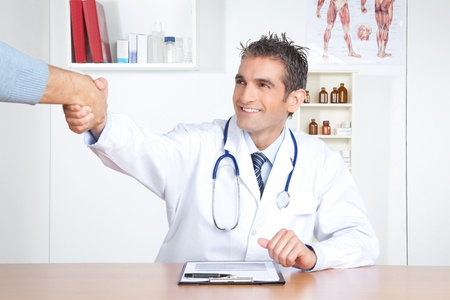 general: Young male doctor and patient shake hands at clinic