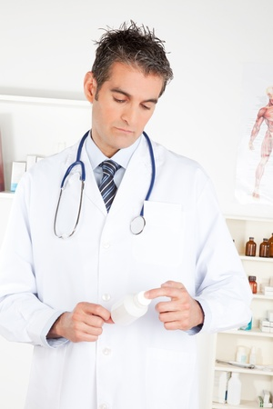 Male doctor holding a bottle of pills  photo