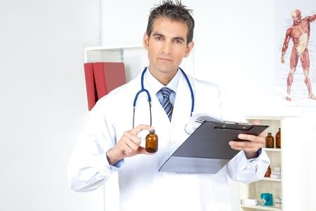 Médico mirando portapapeles con una botella Foto de archivo - 12766685