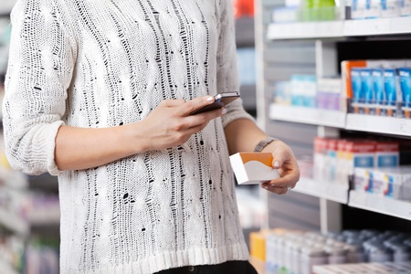 Mid-section of woman holding medication box and dialing on cell phone photo