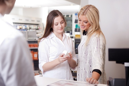 Female Pharmacist Advising Customer At Pharmacy at Cashier  photo